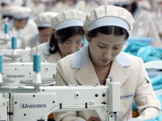 "North Korean workers work at a factory of South Korean apparel maker Shinwon in the inter-Korean industrial park in Kaesong, just a few hundred metres (yards) north of the heavily fortified Demilitarised Zone (DMZ) that divides the Korean peninsula, 26 May 2005. A South Korean minister said 26 May that ""serious give-and-take"" was needed to break the nuclear impasse with North Korea and that Seoul had a proposal, a week after failing to get Pyongyang back to disarmament talks. AFP PHOTO/POOL/LEE Jae-Won / AFP PHOTO / POOL / LEE JAE-WON"