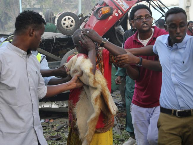 Somalis help a wounded man who was injured in a horror attack in Mogadishu. Picture: AP Photo/Farah Abdi Warsameh