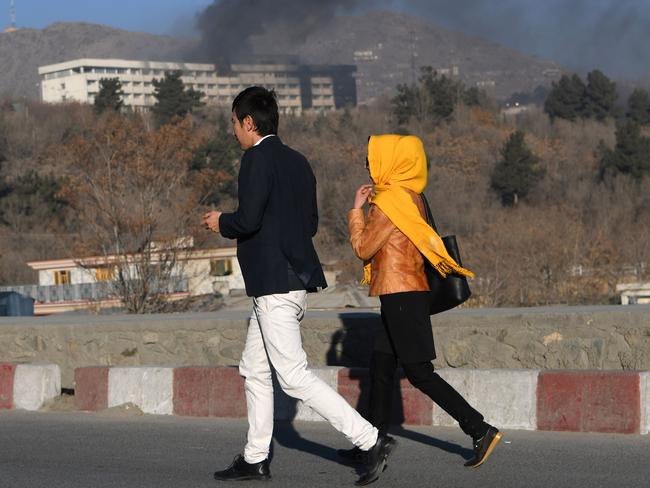 fghans walk near the Intercontinental Hotel as smoke billows during a fight between gunmen and Afghan security forces in Kabul. Picture: AFP