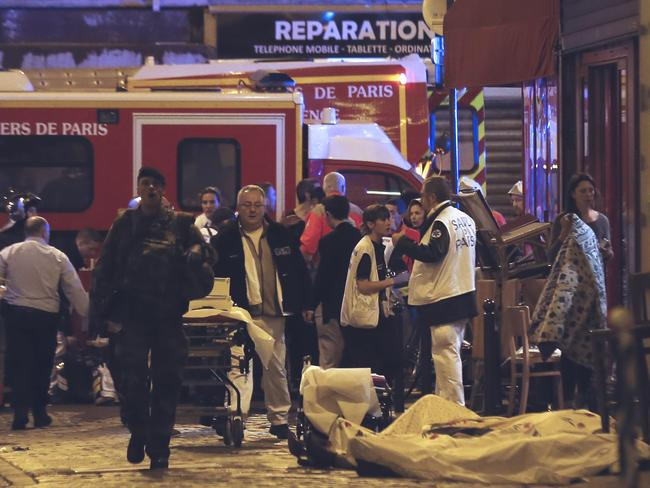 Chaos ... Police officers and rescue workers gather around a victim outside in the 10th district of Paris. Picture: AP Photo/Jacques Brinon