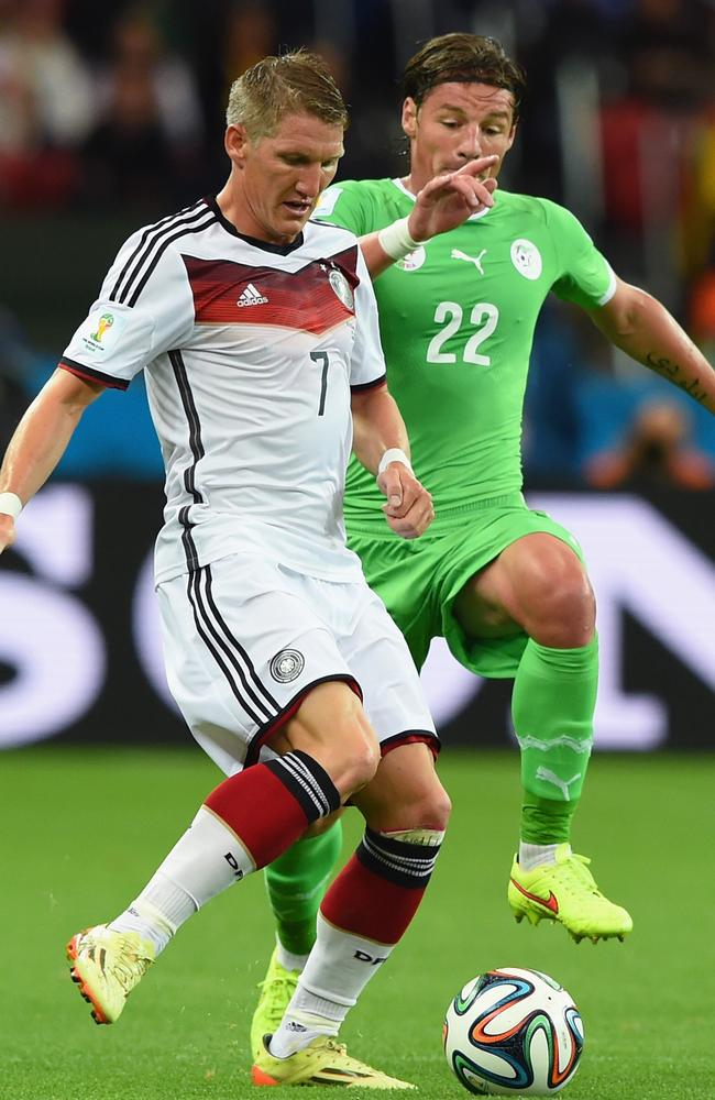 Bastian Schweinsteiger of Germany and Mehdi Mostefa of Algeria compete for the ball.