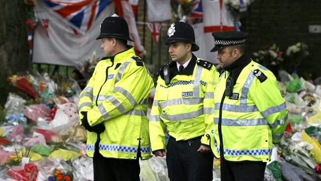 Police officers stand guard near the thousands of tributes left in honour of Lee Rigby. Picture: AP