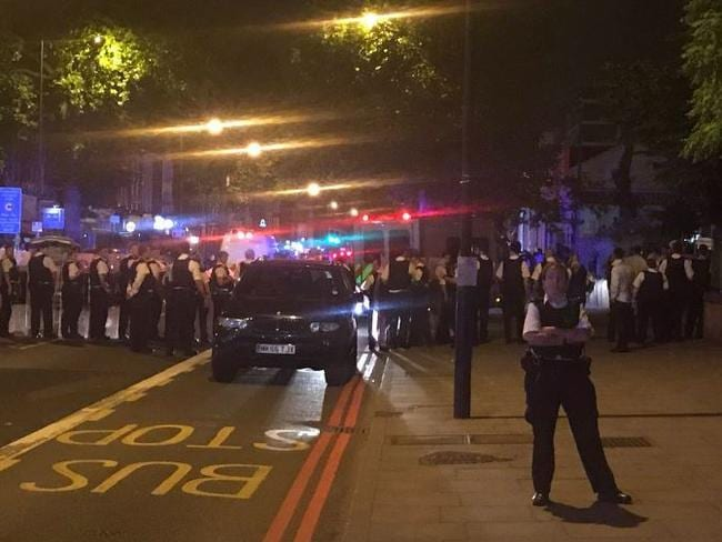 Police with shields block a street in Stamford Hill in a bid to disperse the armed young people. Picture: Samir Jeraj