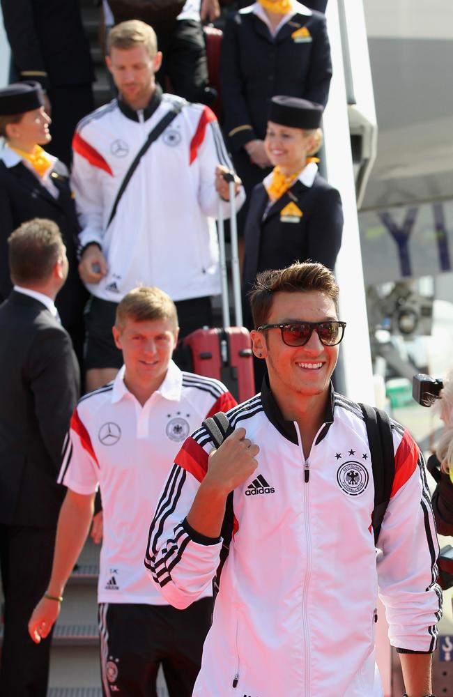 Mesut Oezil smiles as he leads the German players off the plane and onto the Berlin airport tarmac.