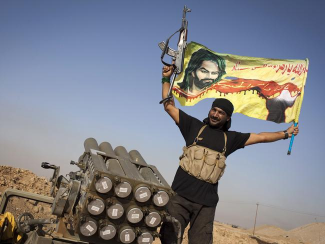 An Iraqi militia fighter from Shiite cleric Moqtada al-Sadr's Saraya al-Salam (Peace Brigade), waves a flag next to a rocket launcher during heavy clashes with Islamic State. AFP PHOTO/ JM Lopez