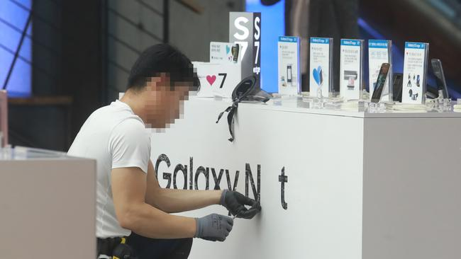 An employee removes stickers advertising Samsung Electronics' Galaxy Note 7 at a sales booth in Seoul. Picture: AAP
