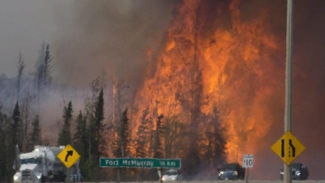 Heatwaves are seen as cars and trucks try and get past the wildfire near Fort McMurray. The fire could have been ignited by lightning.