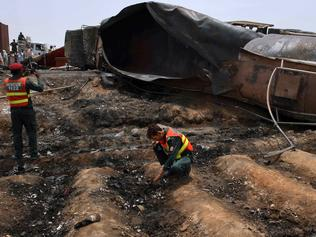 Pakistani rescue workers examine the site of an oil tanker explosion at a highway near Bahawalpur, Pakistan, Sunday, June 25, 2017. An overturned oil tanker burst into flames in Pakistan on Sunday, killing more than one hundred people who had rushed to the scene of the highway accident to gather leaking fuel, an official said. (AP Photo/Iram Asim)