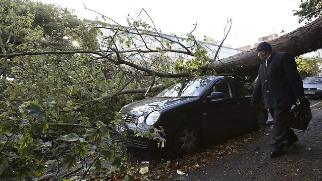 A man looks at a car crushed under a fallen tree following a storm in Hornsey, north London, Monday, Oct. 28, 2013. A major storm with hurricane-force winds is lashing southern Britain, causing flooding and travel delays including the cancellation of roughly 130 flights at London's Heathrow Airport. (AP Photo/PA, Yui Mok) UNITED KINGDOM OUT, NO SALES , NO ARCHIVES