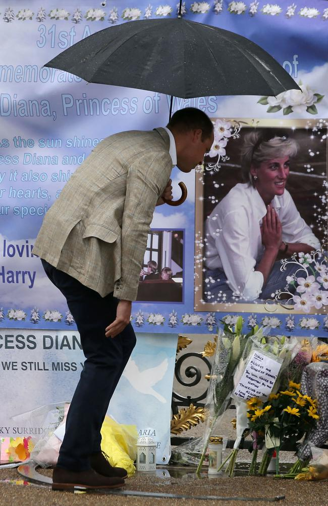 Britain's Prince William, Duke of Cambridge looks at tributes left by members of the public at one of the entrances of Kensington Palace to mark the coming 20th anniversary of the death of Diana. Picture: AFP