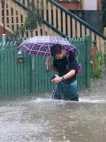 Rigby Wilshire wades through fllood waters to get to his home on Longlands st at East Brisbane. Rain from ex-cyclone Debbie causing flooding in Brisbane. Pic Darren England.
