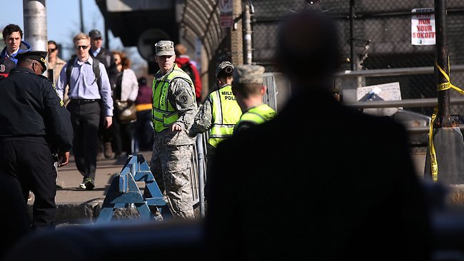 BOSTON, MA - APRIL 17: People walk to work by National Guardsman near the scene of twin bombings at the Boston Marathon on April 17, 2013 in Boston, Massachusetts. The explosions, which occurred near the finish line of the 116-year-old Boston race on April 15, resulted in the deaths of three people with more than 170 others injured. Security has been heightened across the nation as the search continues for the person or people behind the bombings. Spencer Platt/Getty Images/AFP== FOR NEWSPAPERS, INTERNET, TELCOS & TELEVISION USE ONLY ==