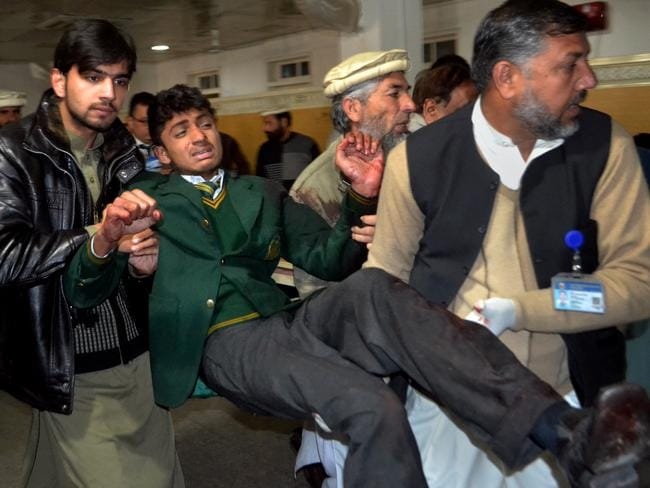 Injured ... Pakistani volunteers help carry injured students into hospital. Picture: AP/Mohammad Sajjad