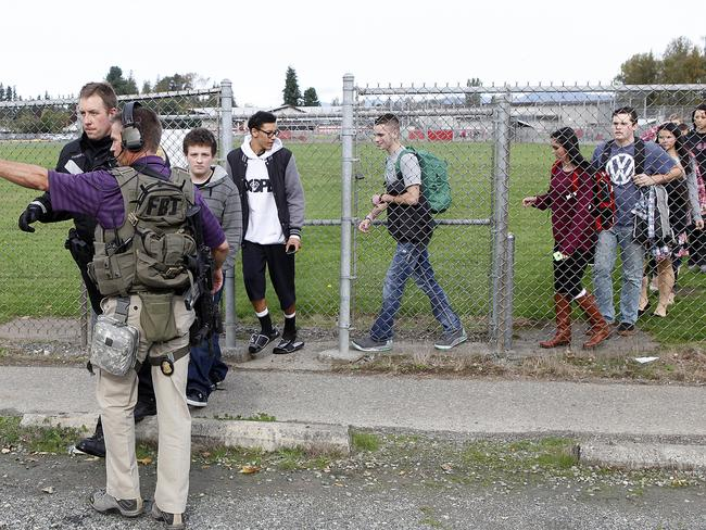 An FBI officer (at left) helps guide students off of the Marysville-Pilchuck High School campus following the shooting.