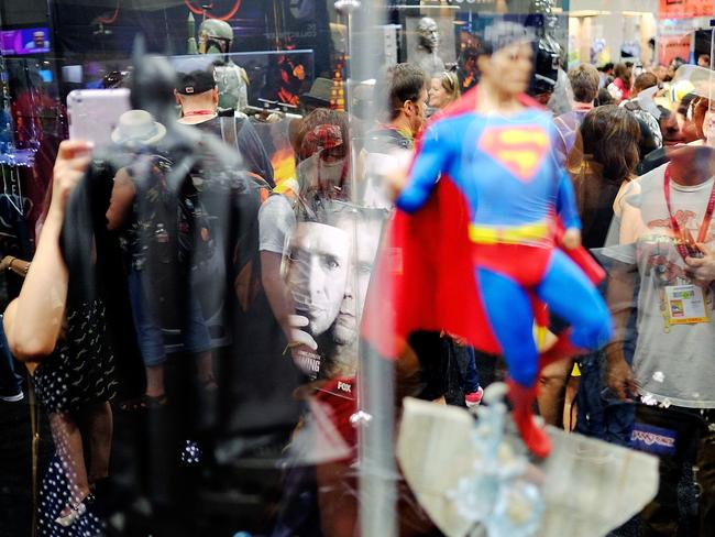 Comic-con madness ... Attendees are reflected in the display case of Batman and Superman figurines in the exhibitor hall during the 45th annual San Diego Comic-Con.