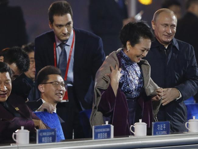 Vladimir Putin helps the Chinese First Lady keep warm.