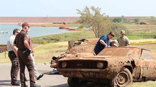 Police inspect one of two cars found containing skeletons at the bottom of Foss Lake, Oklahoma.