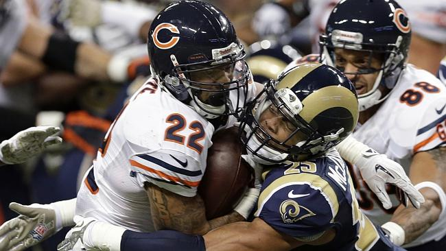 Chicago Bears running back Matt Forte, left, runs with the ball as he is pulled down by St. Louis Rams safety T.J. McDonald.
