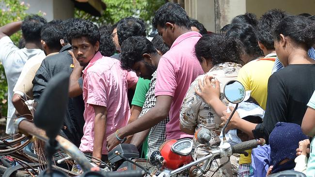 Sri Lankan asylum seekers sent back by Australia queue to enter the magistrates' court in the southern port district of Galle.