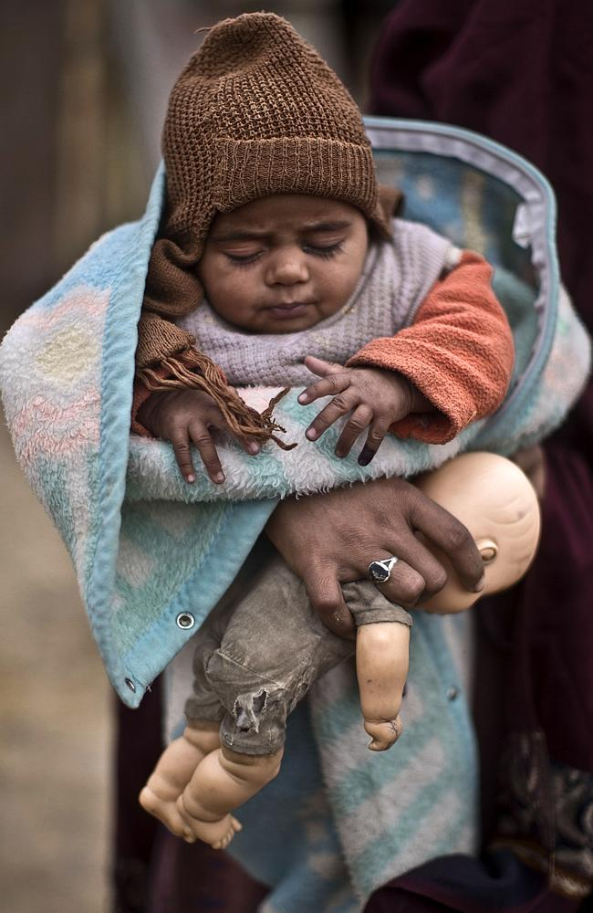 A Pakistani woman holds her child after the administration of a polio vaccine.