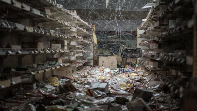 An aisle of a supermarket with products left on the floor. Since the disaster nature has been at work and cobwebs now hang between the shelves. Picture: Arkadiusz Podniesinski/REX Shutterstock