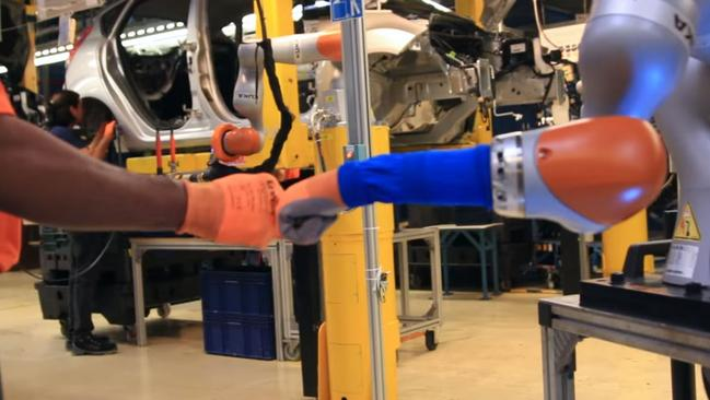 Cobots work hand-in-hand with production line workers to fit shock absorbers to the Fiesta at Ford's Cologne plant in Germany.