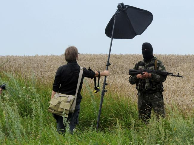 A masked armed separatist militant poses for a photographer near the crash site