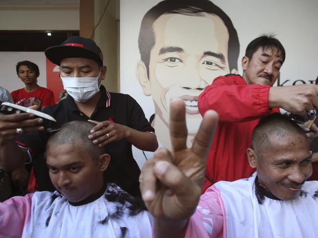 Celebrating ... Supporters of Mr Joko cut their hair to celebrate his election win. Picture: AP
