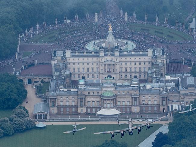 Celebrations ... a Lancaster and two Spitfires fly over Buckingham Palace as part of The Queen's Birthday Flypast. Picture: Matt Cardy