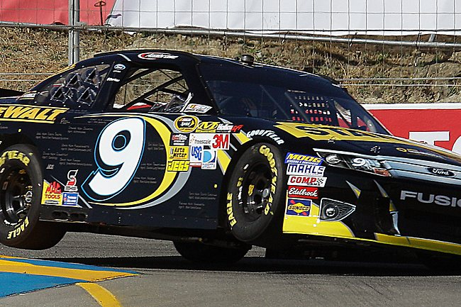 Driver Marcos Ambrose of Australia, goes up on two wheels as he rounds a turn during practice for Sunday's NASCAR Sprint Cup Series auto race Saturday, June 23, 2012, in Sonoma, Calif. (AP Photo/Ben Margot)