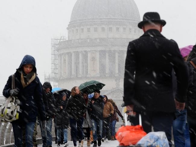 Pedestrians walk over the Millennium Bridge near St Paul's Cathedral as snow falls over central London. Picture: AFP