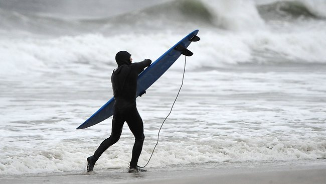 There's always one... a surfer out to make the best of the violent sea. Picture: AP