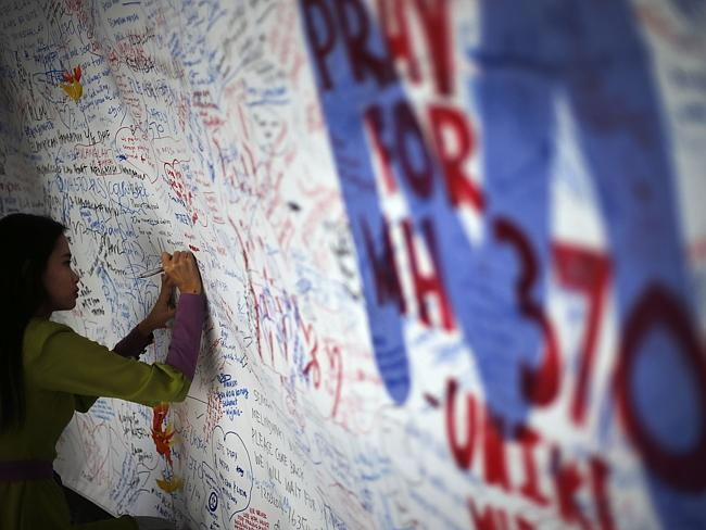 "Still hope?...A woman writes a message of support for those missing in the disappearance of Malaysia Airlines flight MH370. Seven days after it vanished, Malaysia admitted for the first time that the plane continued to fly for seven hours after losing contact, and blamed ""deliberate actions""."