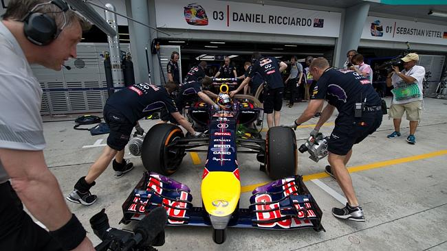 Getting ready ... Red Bull team crew members prepare Daniel Ricciardo's car during the second practice session ahead of the race in Malaysia. Picture: AFP