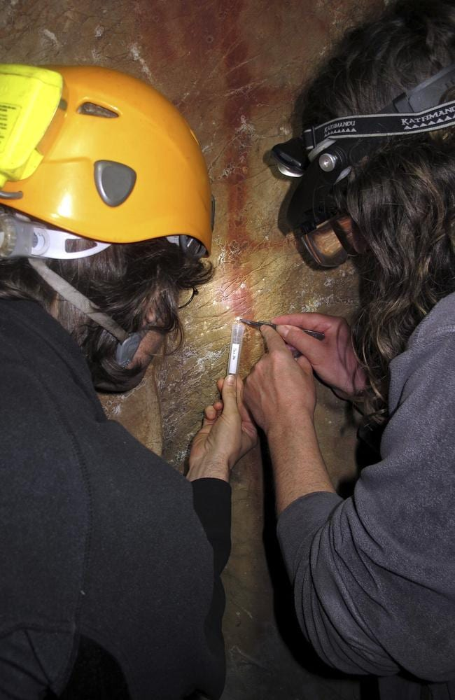 Dirk Hoffmann and Alistair Pike take a sample from a calcite crust on top of a red ladder-shaped cave painting.