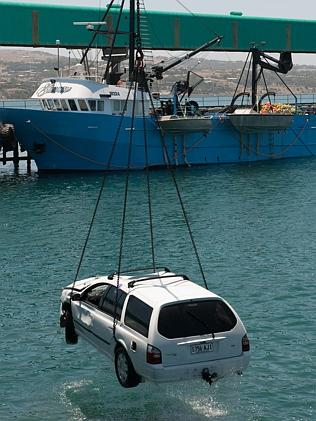 Damien Little's Ford station wagon is lifted from the water. Picture: Ivon Perrin