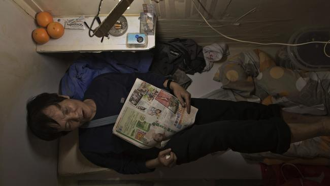 A resident known only by his surname Yeung is seen resting in their home, surrounded by his belongings. Picture: Kin Cheung/AP