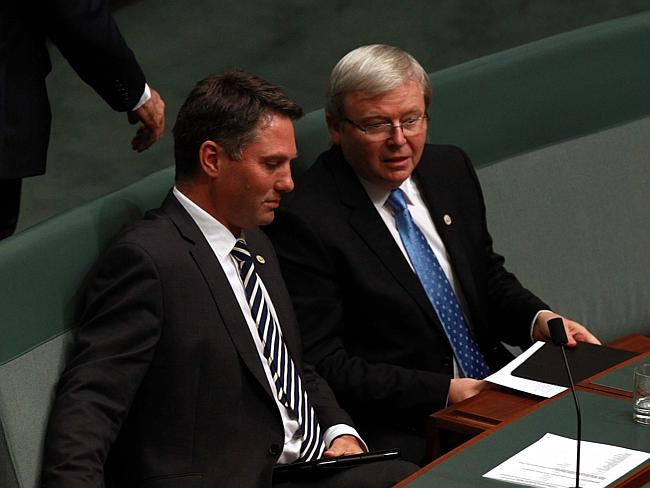 Richard Marles and Kevin Rudd discuss business during Question time in Parliament House.