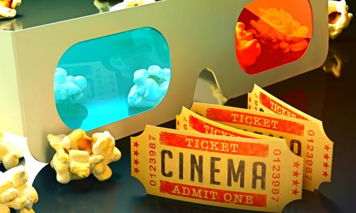 Movie ticket and 3D glasses with popcorn scattered around.