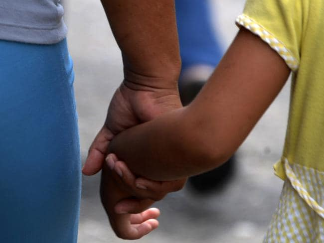 Fifty-two-year-old Geraldina, who had three sons killed by gang members, takes her daughter by the hand as they walk through a street in Honduras. Picture: Orlando Sierra/AFP