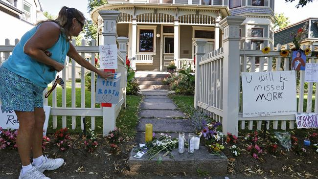"Boulder resident Wendy Darling tapes up a sign that reads ""Fly Be Free Robin,"" as she pays tribute to Robin Williams at a makeshift memorial outside the home where the 80s TV series ""Mork & Mindy,"" was filmed. Picture: Brennan Linsley"