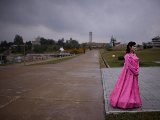 A North Korean tour guide wearing a traditional 'hanbok' dress waits for visitors.