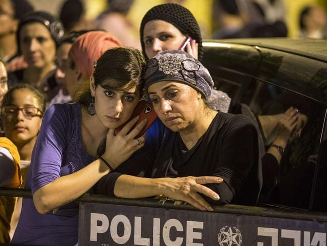 Mass grief ... Israelis gather near one of the teens' houses after the bodies were found.