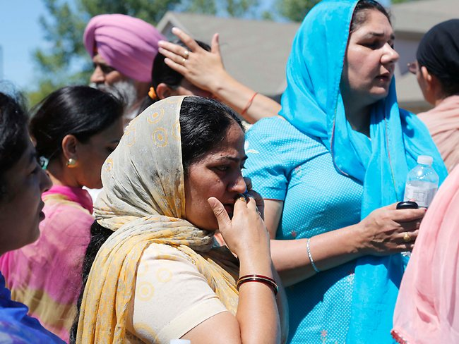 Bystanders stand outside the scene of a shooting inside The Sikh Temple in Oak Creek, Wiscinsin, Sunday, Aug. 5, 2012. Police in Wisconsin say at least seven people are dead at a Sikh temple near Milwaukee, including the suspected gunman. AP Photo/Jeffrey Phelps