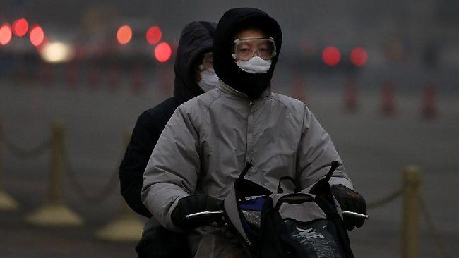 A man and his son wearing the mask ride the electric bicycle during severe pollution on January 30, 2013 in Beijing, China.