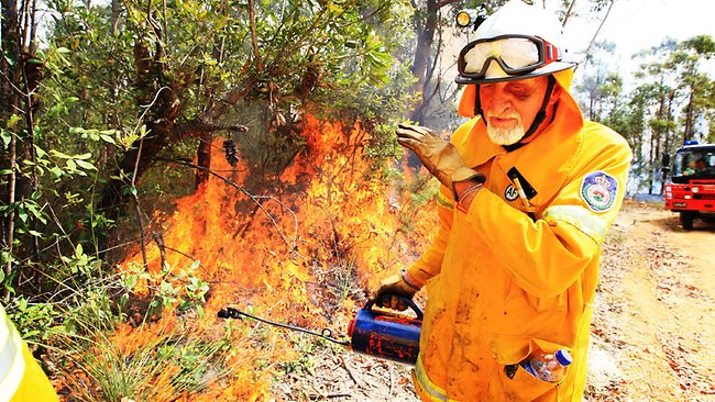 Firefighter Alan Harris shields his face from the heat as he lights a containment line around the Dean's Gap fire in Conjola National Park. Picture: Craig Greenhill