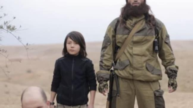 Chilling images ... a child soldier executes Russian spies in an Islamic State video.