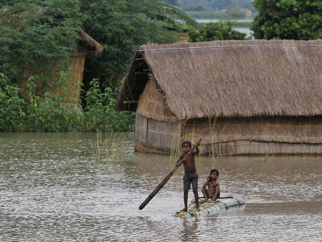 A boy rows a banana raft in a flood-affected area. Picture: Anupam Nath