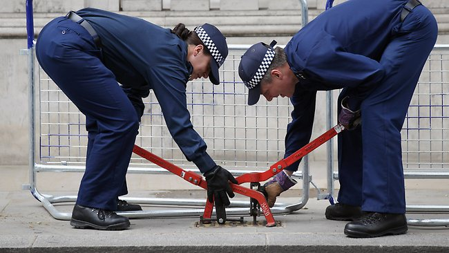 LONDON, ENGLAND - JUNE 01: Two police officers examine beneath a manhole cover on Whitehall on June 1, 2012 in London, England. With two days to go before the start of the Diamond Jubilee celebrations final preparations are taking place in the capital. (Photo by Oli Scarff/Getty Images)