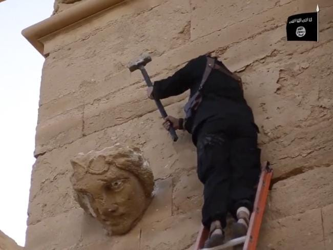 In this image made from a militant video posted on YouTube on Friday, April 3, 2015, a militant hammers away at a face on a wall in Hatra.